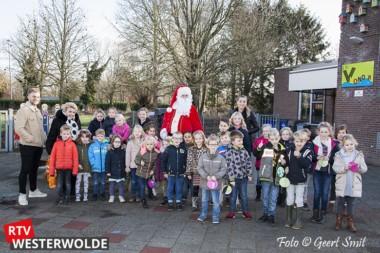 Kinderen helpen kerstman met boom versieren